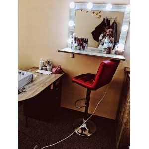 A mirror for a makeup artist or hairdresser with a wide shelf.